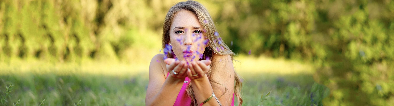 Imagen de una chica soplando unos pétalos